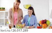 Купить «happy family cooking salad at home kitchen», видеоролик № 26017289, снято 5 апреля 2017 г. (c) Syda Productions / Фотобанк Лори