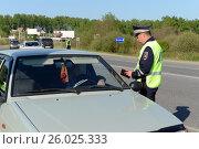 Купить «Инспектор дорожно-патрульной службы полиции проверяет документы водителя автмобиля», фото № 26025333, снято 14 мая 2016 г. (c) Free Wind / Фотобанк Лори