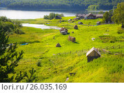 View from the hill on a few houses on the bank of the green grassy bank of river and the forest in the background in summer in Kenozersky National Park, Arkhangelsk region, Russia (2015 год). Редакционное фото, фотограф Алексей Мараховец / Фотобанк Лори
