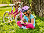 Child traveling bicycle in summer park. Girl watch tablet computer., фото № 26058369, снято 6 апреля 2016 г. (c) Gennadiy Poznyakov / Фотобанк Лори