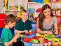 Preschool scissors in kids hands cutting paper with teacher in class., фото № 26058393, снято 25 марта 2017 г. (c) Gennadiy Poznyakov / Фотобанк Лори