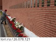 Купить «Женщина кладет красные гвоздики к надгробию советских функционеров у кремлевской стены на Красной площади в городе Москве, Россия», фото № 26078121, снято 22 апреля 2017 г. (c) Николай Винокуров / Фотобанк Лори