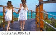 Little adorable girls on a wooden bridge running to the beach in luxury vacation. Стоковое видео, видеограф Дмитрий Травников / Фотобанк Лори