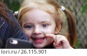 Little Girl on nature watching cartoons. Стоковое видео, видеограф Потийко Сергей / Фотобанк Лори