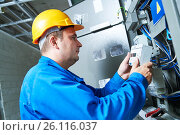 Купить «Electrician installing energy saving meter», фото № 26116037, снято 19 августа 2016 г. (c) Дмитрий Калиновский / Фотобанк Лори