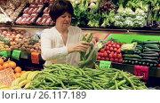Купить «Mature woman buying green beans at market», видеоролик № 26117189, снято 23 марта 2017 г. (c) Яков Филимонов / Фотобанк Лори