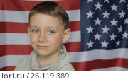 Купить «The boy's portrait against the background of the American banner. Close up», видеоролик № 26119389, снято 30 апреля 2017 г. (c) Олег Башкир / Фотобанк Лори