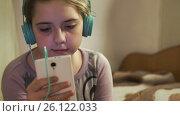 Купить «Girl with headphones listening music from smartphone», видеоролик № 26122033, снято 29 апреля 2017 г. (c) Кузьмов Пётр / Фотобанк Лори