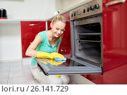 happy woman cleaning cooker at home kitchen. Стоковое фото, фотограф Syda Productions / Фотобанк Лори