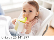 Купить «baby drinking from spout cup in highchair at home», фото № 26141877, снято 24 января 2017 г. (c) Syda Productions / Фотобанк Лори