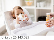 Купить «baby drinking from spout cup in highchair at home», фото № 26143085, снято 24 января 2017 г. (c) Syda Productions / Фотобанк Лори