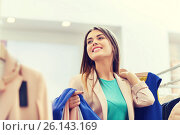 Купить «happy young woman choosing clothes in mall», фото № 26143169, снято 19 февраля 2016 г. (c) Syda Productions / Фотобанк Лори
