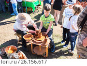 Купить «Учитель помогает ученику по работе с глиной при изготовлении керамики на гончарном круге», фото № 26156617, снято 24 сентября 2018 г. (c) FotograFF / Фотобанк Лори