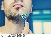 Serious guy shaving his beard. Стоковое фото, фотограф Dmitriy Melnikov / Фотобанк Лори
