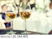 Купить «two glasses of white whine outdoors», фото № 26184405, снято 22 сентября 2015 г. (c) Дмитрий Калиновский / Фотобанк Лори