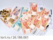 Купить «Металлические деньги и бумажные купюры лежат на счётах на квартплату крупным планом», фото № 26186061, снято 15 марта 2017 г. (c) Максим Мицун / Фотобанк Лори