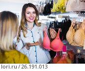 Купить «Female seller demonstrating client bras in underwear store», фото № 26191013, снято 20 марта 2017 г. (c) Яков Филимонов / Фотобанк Лори