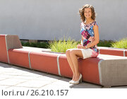 Купить «Young woman is sitting on the bench», фото № 26210157, снято 29 июня 2011 г. (c) Tatjana Romanova / Фотобанк Лори