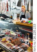 Купить «Salesman offering different sausages», фото № 26220233, снято 5 октября 2016 г. (c) Яков Филимонов / Фотобанк Лори