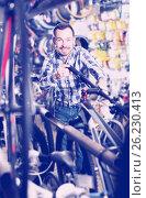 Купить «Man considers bicycle handlebar in store», фото № 26230413, снято 27 июня 2019 г. (c) Яков Филимонов / Фотобанк Лори