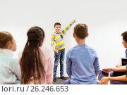 Купить «happy student boy showing something at white wall», фото № 26246653, снято 23 октября 2016 г. (c) Syda Productions / Фотобанк Лори