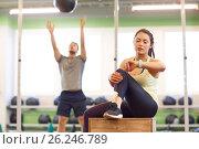 Купить «man and woman with ball and fitness tracker in gym», фото № 26246789, снято 19 февраля 2017 г. (c) Syda Productions / Фотобанк Лори