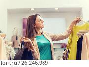 Купить «happy young woman choosing clothes in mall», фото № 26246989, снято 19 февраля 2016 г. (c) Syda Productions / Фотобанк Лори