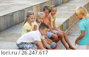 Купить «cheerful boys and girls in school age sitting and playing with ball outdoors», видеоролик № 26247617, снято 20 сентября 2016 г. (c) Яков Филимонов / Фотобанк Лори