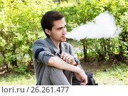 Купить «Задумчивый молодой бизнесмен курит электронную сигарету в парке», фото № 26261477, снято 12 мая 2017 г. (c) Круглов Олег / Фотобанк Лори