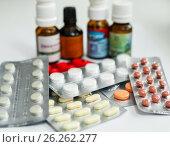Таблетки и баночки с лекарствами лежат на белом фоне (2017 год). Редакционное фото, фотограф Игорь Низов / Фотобанк Лори