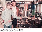 Купить «Father and teenage son examining drum units in guitar shop», фото № 26265489, снято 29 марта 2017 г. (c) Яков Филимонов / Фотобанк Лори