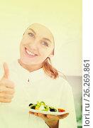 Купить «portrait of young coosie woman showing salad at kitchen», фото № 26269861, снято 7 декабря 2019 г. (c) Яков Филимонов / Фотобанк Лори