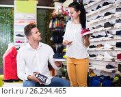 Купить «Assistant helping customer to choose sneakers», фото № 26294465, снято 22 ноября 2016 г. (c) Яков Филимонов / Фотобанк Лори