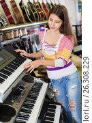 Купить «Smiling young girl choosing synthesizer», фото № 26308229, снято 19 августа 2018 г. (c) Яков Филимонов / Фотобанк Лори