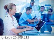 Купить «Composite image of beautiful smiling doctor typing on keyboard with her team behind», фото № 26309213, снято 19 июля 2018 г. (c) Wavebreak Media / Фотобанк Лори
