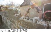 Купить «Rural man laying cinder blocks», видеоролик № 26319745, снято 15 мая 2017 г. (c) Илья Шаматура / Фотобанк Лори