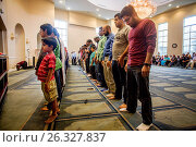 Muslim men bow in reverence during Friday afternoon prayers at religious services at an Anaheim, CA, mosque. Note boy at left. (2016 год). Редакционное фото, фотограф Spencer Grant / age Fotostock / Фотобанк Лори