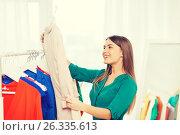 Купить «happy woman choosing clothes at home wardrobe», фото № 26335613, снято 19 февраля 2016 г. (c) Syda Productions / Фотобанк Лори