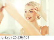 Купить «woman with tweezers tweezing eyebrow at bathroom», фото № 26336101, снято 13 февраля 2016 г. (c) Syda Productions / Фотобанк Лори