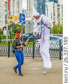 Купить «Клоун на ходулях вручает рекламный листок в Митине», эксклюзивное фото № 26337189, снято 18 мая 2017 г. (c) Виктор Тараканов / Фотобанк Лори