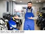Купить «professional man worker displaying various motorcycles in workshop», фото № 26359689, снято 21 сентября 2019 г. (c) Яков Филимонов / Фотобанк Лори