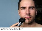 Young man shaving his beard with electric shaver. He shaved half of beard. Стоковое фото, фотограф Dmitriy Melnikov / Фотобанк Лори