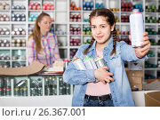 Купить «Portrait of girl choosing paint color in aerosol can in art shop», фото № 26367001, снято 12 апреля 2017 г. (c) Яков Филимонов / Фотобанк Лори
