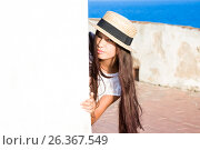Girl in straw hat peeks out from behind wall. Стоковое фото, фотограф Papoyan Irina / Фотобанк Лори