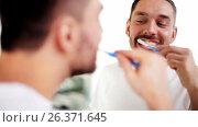 man with toothbrush cleaning teeth at bathroom. Стоковое видео, видеограф Syda Productions / Фотобанк Лори
