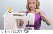Купить «Девочка подросток готовит к работе швейную машинку,заправляет нить», видеоролик № 26377729, снято 27 мая 2017 г. (c) Круглов Олег / Фотобанк Лори