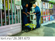 Мужчина покупает дешевую рыбу в ларьке с надписью на армянском языке. Акция для сига 5 штук -1000 драм.  Ереван, Армения, фото № 26381673, снято 17 мая 2017 г. (c) Эдуард Паравян / Фотобанк Лори