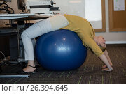 Купить «Executive performing stretching exercise on fitness ball», фото № 26394645, снято 5 марта 2017 г. (c) Wavebreak Media / Фотобанк Лори