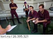 Serious baseball team planning while sitting on bench. Стоковое фото, агентство Wavebreak Media / Фотобанк Лори