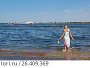 Volgograd, Russia - May 08, 2012: Blond woman paddling her bare feet during a flood in the background of the Volga River with a boat. Стоковое фото, фотограф Юлия Олейник / Фотобанк Лори